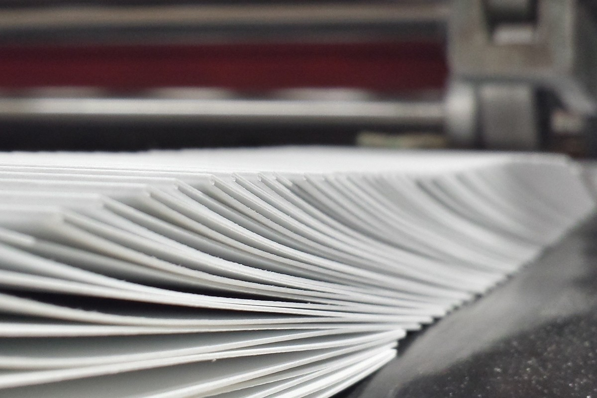 Photograph showing the folding process, with folded tags coming off our mechanical folder.