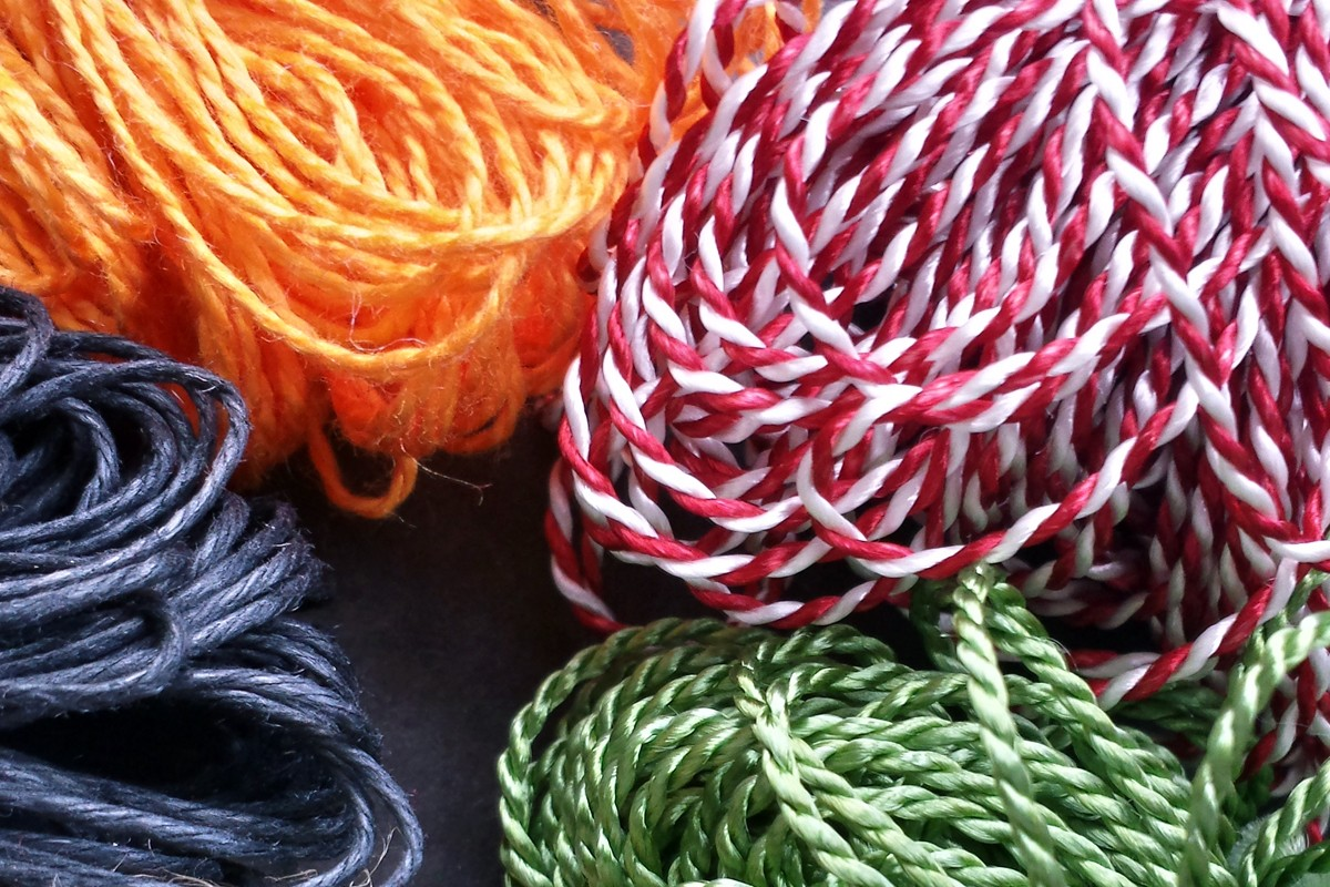 Photograph of bundles of knotted loops; from top left: dark orange mercerized cotton, red-white variegated Pearlray, leaf green heavyweight Pearlray, and black waxed cord.
