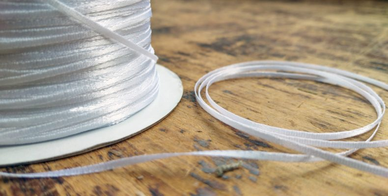 A spool (and a small coiled length) of our new double faced satin ribbon, in white.