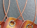 Ochre and saffron striped tags with nickel eyelets strung with our copper metallic elastic.