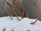 White tags with clipped corners strung with our copper metallic elastic.