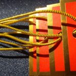 Vermilion tags with a gold foil border strung with our gold metallic elastic.