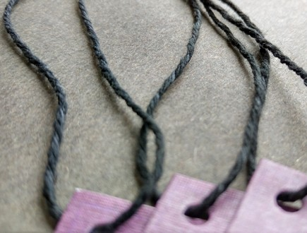 Purple tags strung with our heavyweight black cotton string.