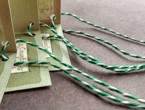 Folded tags strung with heavyweight variegated green-white cotton string.