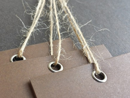 Brown folded tags with brass eyelets strung with our jute twine.