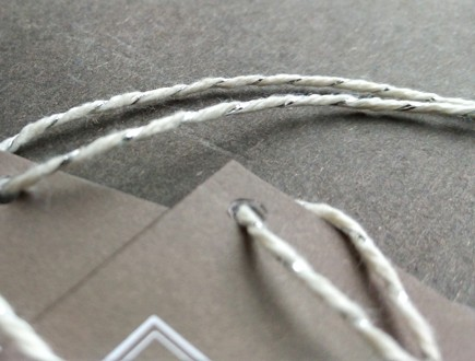 Folded tags in a neutral hue strung with our silver-white metallic yarn.