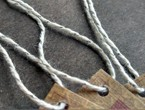 Folded tags with textured paper strung with our silver-white metallic yarn.