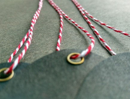 Eyeletted oval tags strung with middle-weight variegated red-white cotton string.