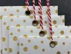 Cream-colored envelopes with gold polka dots strung with our red-white variegated Pearlray.