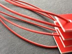 Red garment tags strung with our red metallic elastic.