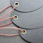 Ovular black tags with brass eyelets strung with red waxed cord.