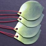 Green folded lime-shaped die-cut tags with red waxed cord.