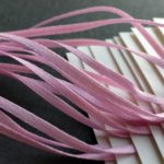 "White tags strung with light pink 1/16"" double-faced satin ribbon."