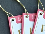 Pink and white tags with gold copy strung with standard elastic in antique gold.