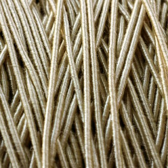 A spool of our standard elastic in antique gold.