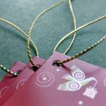 Cranberry-red folded tags with star and dove motifs strung with our gold braid.