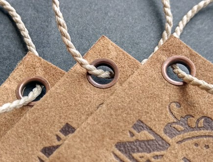 Tags of suede-like cover stock featuring debossed leather-look design and copy, reinforced with our antique copper eyelets and strung with our heavyweight bell cord.