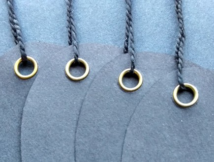 Oval tags of charcoal paper stock reinforced with our brass eyelets and strung with black mercerized cotton string.