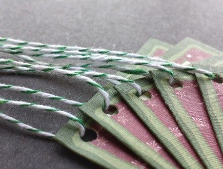 Maroon tags with snowflake graphic and two-tone green border strung with green bakery twine.