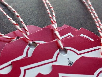 Die-cut red medallion-shaped tags strung with red bakery twine.