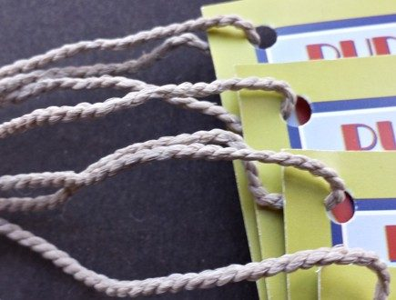Blue, navy, red, and chartreuse tags with Art Deco type strung with heavyweight bell cord.