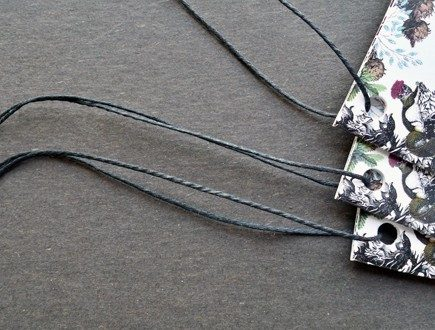 Booklets with foliage motif strung with black waxed cord.