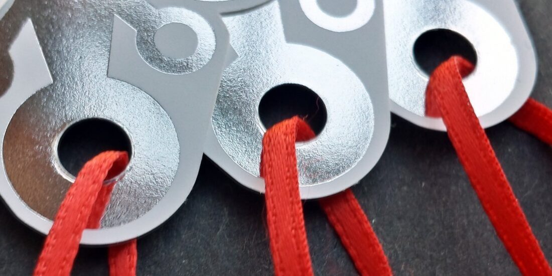 Photograph of elaborate die-cut tags strung with red satin ribbon.