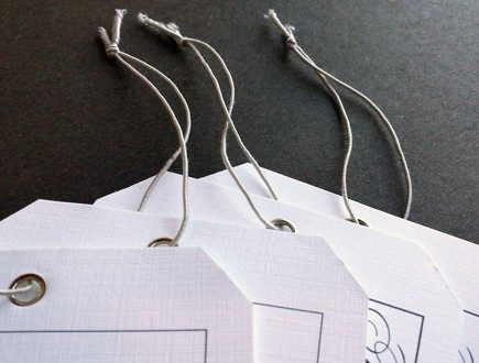 Nickel-eyeletted tags strung with gray non-fray elastic.