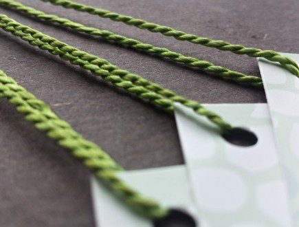 White and light green tags with polka dot pattern strung with green heavyweight Pearlray.
