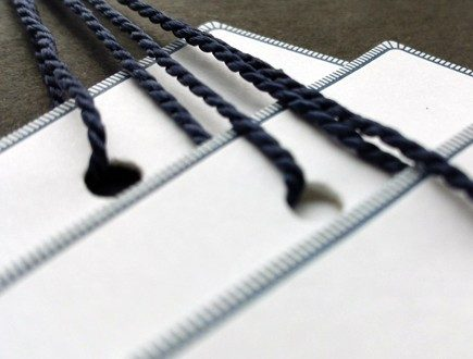 White tags with a fine navy blue brick-course border pattern strung with navy blue heavyweight Pearlray.