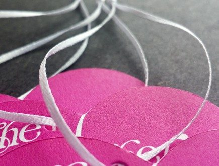Hot pink heart-shaped die-cut tags with white copy strung with white 1/16