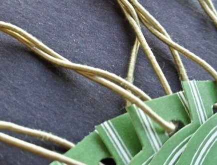 Green die-cut circle tags strung with standard elastic in antique gold.