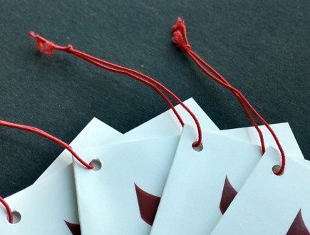 Folded white tags with red logo strung with standard elastic in red.