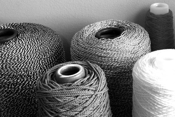 Monochrome photograph showing the different textural qualities of various spools of string.